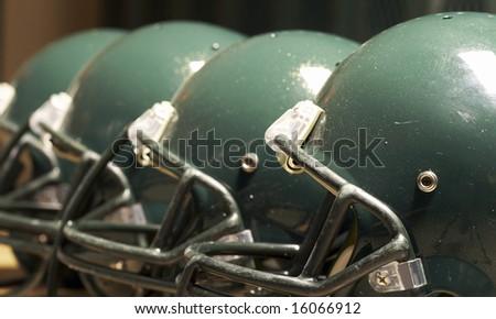 a macro of few football helmet on bench - stock photo