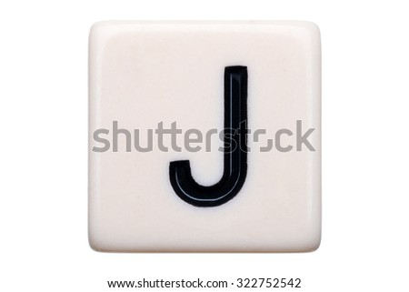 A macro shot of a game tile with the letter J on it on a white background.
