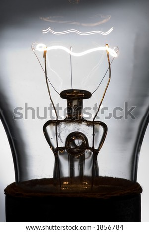 A macro shot of a lightbulb with the filament lit. - stock photo
