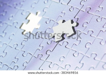 A macro shot of a puzzle. One piece is missing from the puzzle and the missing piece is laying on the puzzle. Image has a vintage effect applied.