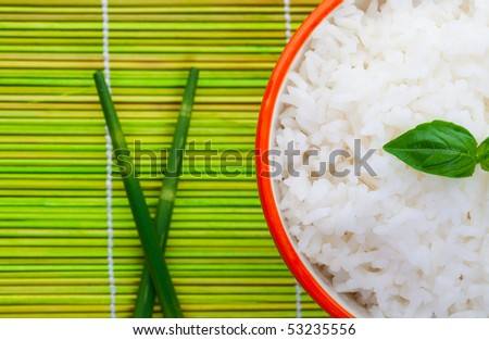 A macro shot of a simple bowl of rice delicately garnished with a sprig of basil. - stock photo