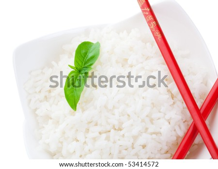 A macro shot of red chopsticks and white rice delicately garnished with a sprig of basil.  Isolated with clipping path. - stock photo