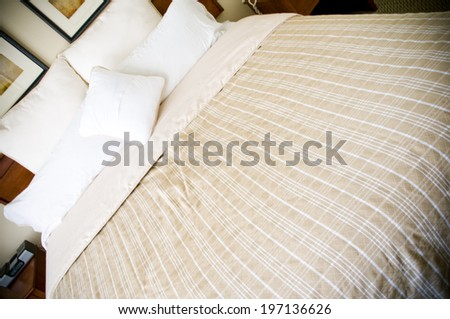 A made bed with pillows, a sheet, and a blanket. - stock photo