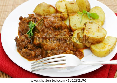 A madras butter beef curry served with curried potatoes and garnished with coriander leaves - stock photo