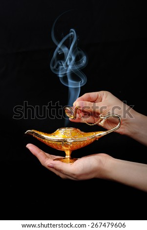 A magic genie lamp on a persons hand - stock photo