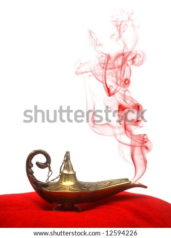 A magical genie lamp with smoke on a red velvet pillow. - stock photo