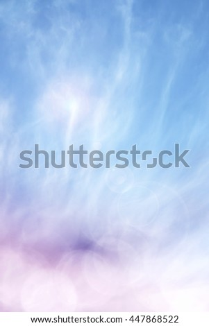 A magical, soft focus sky scene with clouds, fog, lens flare, and abstract bokeh effects.  Image also features a colorful purple to blue gradient. - stock photo