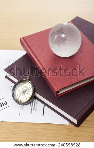 A magnifier, glasses, glass globe, compass, graph paper(document), clipboard and book on the wooden office desk(table). - stock photo