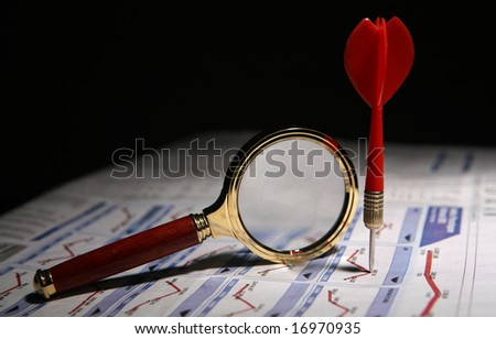 A magnifying glass and a dart on stockmarket news - stock photo