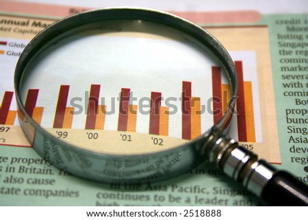 A magnifying glass focusing on a graph in the business section of the newspaper. - stock photo