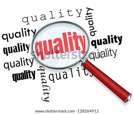 A magnifying glass hovering over several words depicting quality, symbolizing the hunt for the best characteristics or values - stock photo