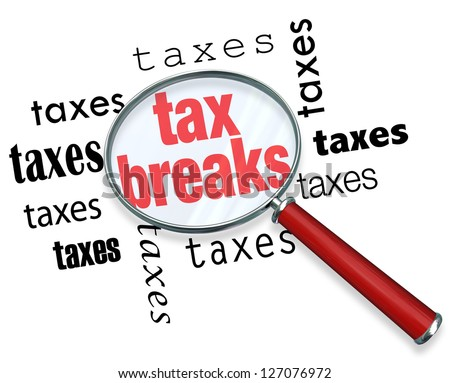 A magnifying glass hovering over the word tax breaks, symbolizing the advice and tricks that an accountant can use to increase deductions and save money when filing tax returns - stock photo