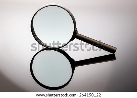 a magnifying glass is on a gray background and reflected - stock photo