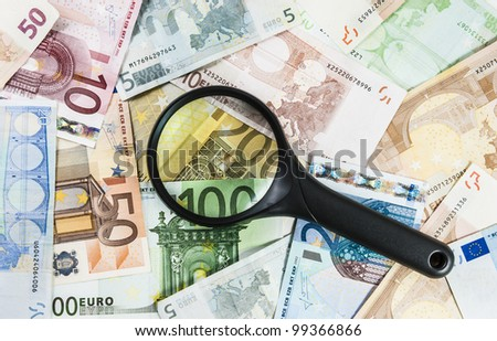 A magnifying glass on different euro bills as a background