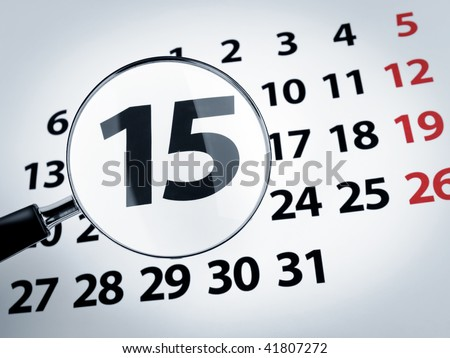 A magnifying glass on the 15th day of a calendar page. - stock photo