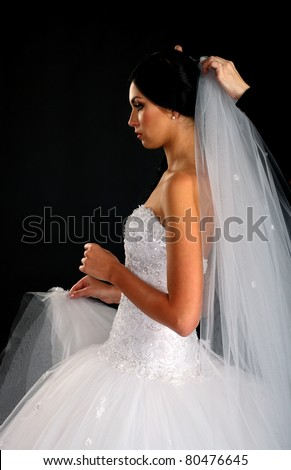 A maid of honor helping the bride with her wedding dress, isolated on black - stock photo