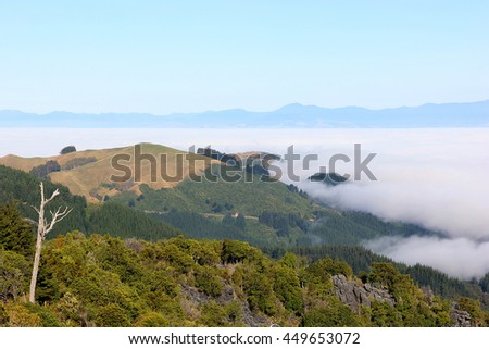 A majestic view over de surrounding mountain tops in the Abel Tasman National Park on the south island of New Zealand. The low hanging clouds cover the valley below. - stock photo