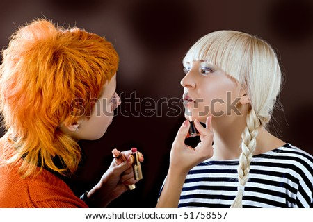 A make-up artist put on make-up to a model - stock photo