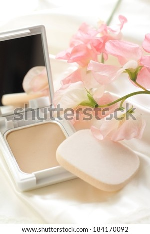 A make up kit with a mirror and pink flowers. - stock photo