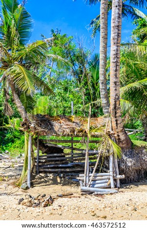 A makeshift shelter on the beach of a tropical island.