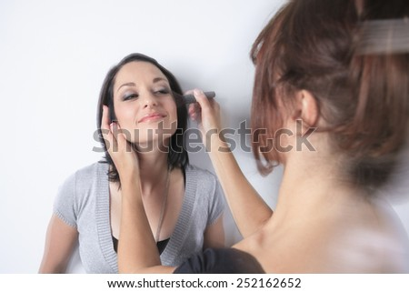 A makeup pro woman working on a fashion model - stock photo