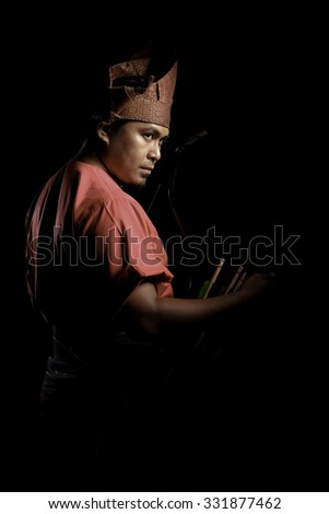 A Malay warrior with his bow and arrow in a traditional malay warrior costume isolated on black background