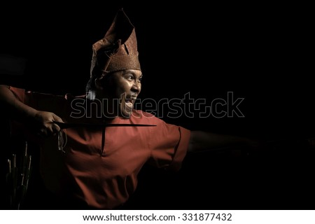 A Malay warrior with his keris ready for a duel in a traditional malay warrior costume isolated on black background - stock photo