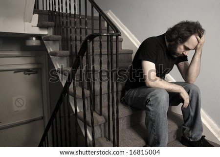A male adult with overwhelming depression sitting in the stairwell of his apartment building.  Desaturated. - stock photo