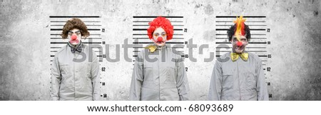 A Male And Two Female Clowns Who Face Criminal Charges Lineup Against A Cement Wall In An Attempt To Find Out The Criminal Amongst The Thugs In A Line Up Of The Usual Suspects - stock photo