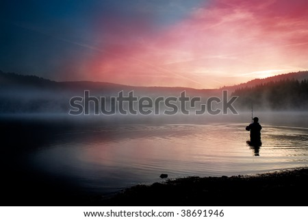a male angler fishing in the river early in the morning - stock photo
