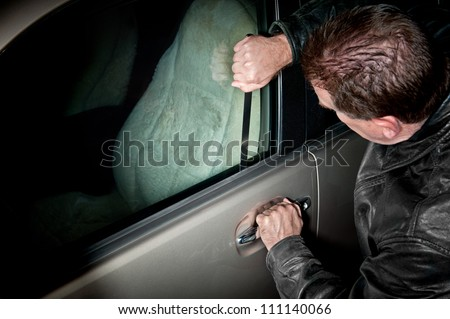 A male car thief uses a flat metal lock pick to break into a vehicle. - stock photo