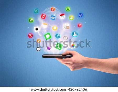A male caucasian hand holding a mobile phone tablet from profile view with digital application logos above the device illustration concept