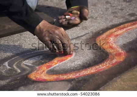 a male chalk artist working on a design - stock photo