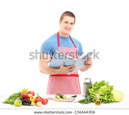 A male chef reading a cookbook while preparing a salad isolated on white background - stock photo