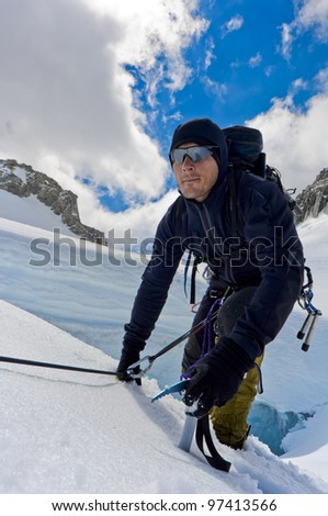 A male climber , dressed in black, climbs up a snowy slope. Winter clear sky day. - stock photo