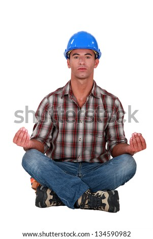 A male construction worker in a yoga position. - stock photo