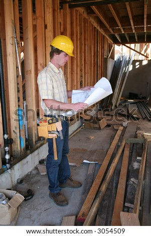 A male construction worker reading the blueprints at a home construction site - stock photo