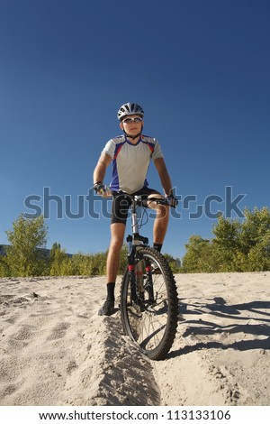 A male cyclist riding a bike stopped rolling on the sand; clear summer day - stock photo