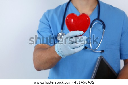 A male doctor holding a heart .