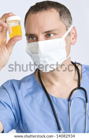 A male doctor in scrubs with a stethoscope examines a sample pot intently - stock photo