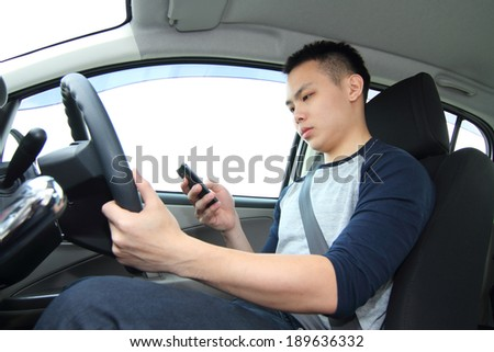 A male driver texting on a cellphone while driving - stock photo