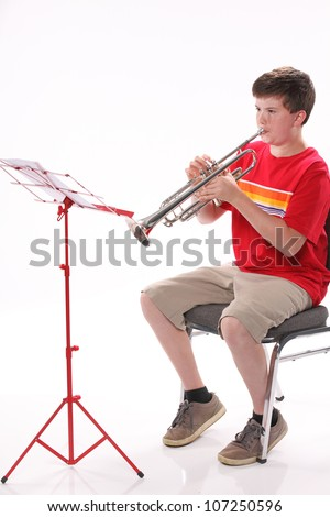A male early teenage boy child playing trumpet facing to the left isolated against a white background with copy space in the vertical format.