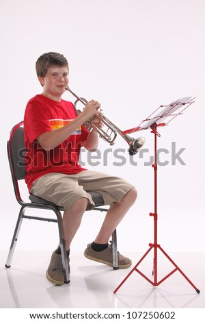 A male early teenage boy child playing trumpet facing to the right isolated against a white background with copy space in the vertical format.