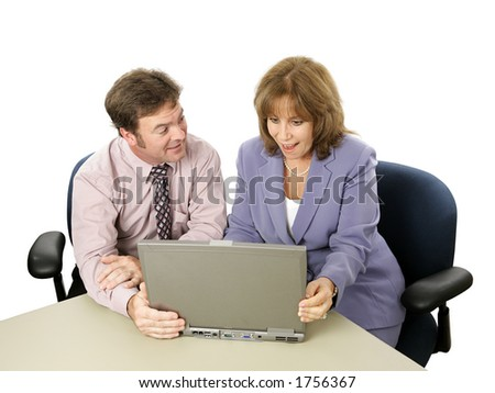 A male-female business team.  He is showing her something surprising on his laptop.