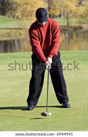 A male golfer smartly dressed in a sweater is enjoying  a round of fall golf.