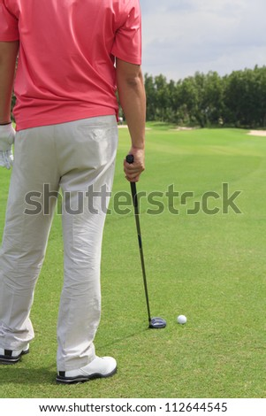 A male golfer standing. Planning for his next shot with a golf club in his hand.