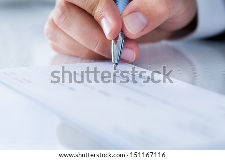 A Male Hand Filling Out The Amount On A Cheque - stock photo