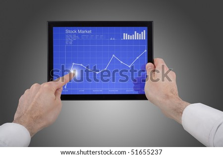 a male hand holding a touchpad pc, one finger touches the screen and checking the stock market