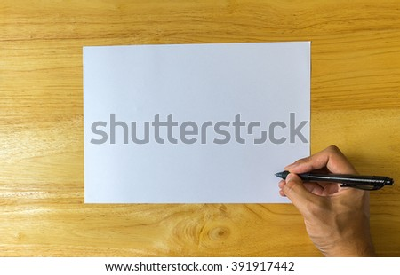 A male hand is writing on a paper on a wooden table. Top view ,Copy space - stock photo