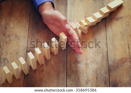 a male hand stoping the domino effect. retro style image executive and risk control concept - stock photo